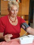 Frau mißt Blutdruck