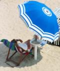 Mann am Strand im Liegstuhl mit Sonnenschirm