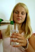 junge Frau füllt Wasserglas